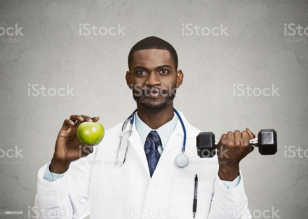 Happy doctor holding green apple, dumbbell stock photo