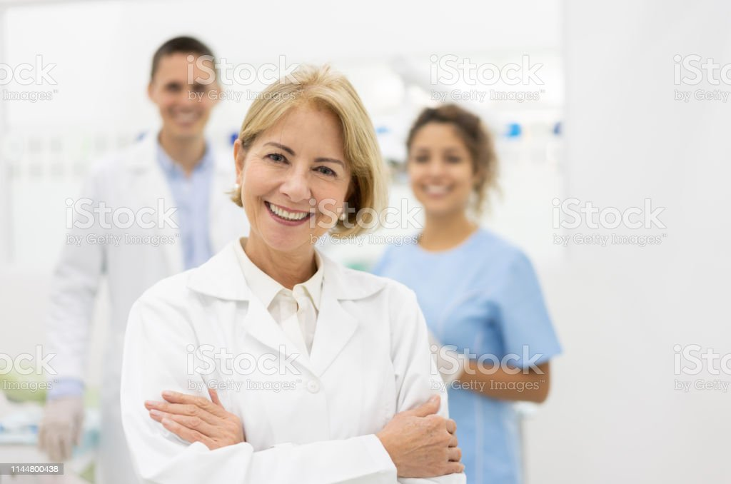 Happy Doctor Leading A Group Of Dentists At The Office Stock