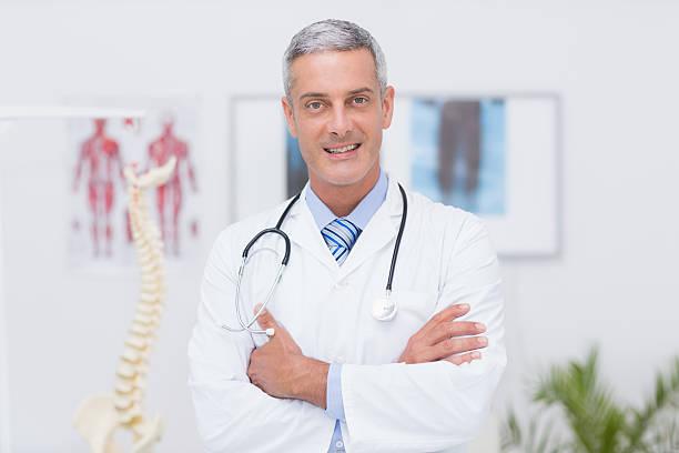 feliz médico, olhando para a câmera com braços cruzados - ortopedia - fotografias e filmes do acervo