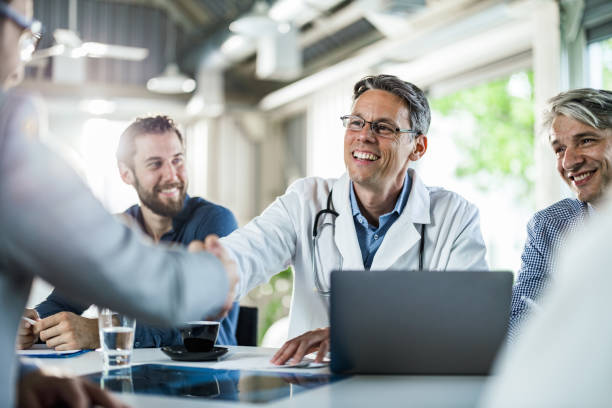 Happy doctor shaking hands with a businessman on a meeting in the office. Happy mid adult doctor welcoming a new colleague during successful job interview in the office. administrator stock pictures, royalty-free photos & images
