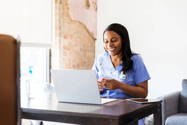 Happy doctor talks with patient during telemedicine appointment stock photo