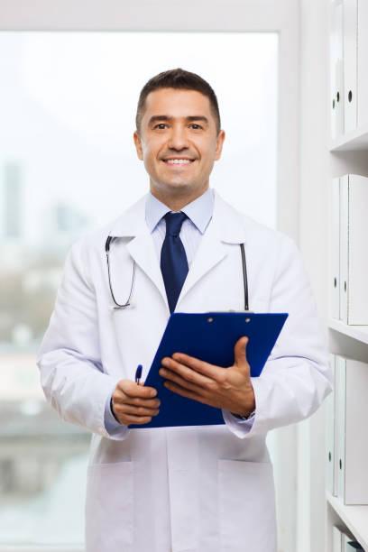 glücklicher Arzt mit Zwischenablage im Arztamt – Foto