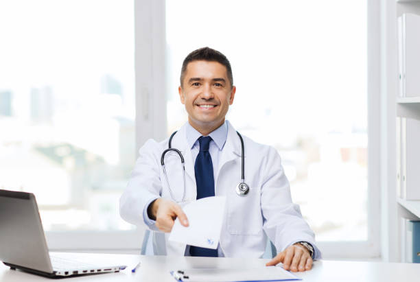 happy doctor with prescription and laptop stock photo