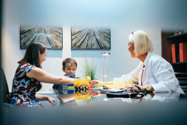 happy doctor woman working and playing with mom and boy - autismus stock-fotos und bilder