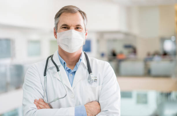 Happy doctor working wearing a facemask to avoid COVID-19 stock photo