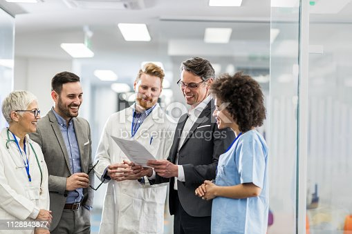 Team of happy doctors and two businessmen cooperating while going through paperwork in a hospital.