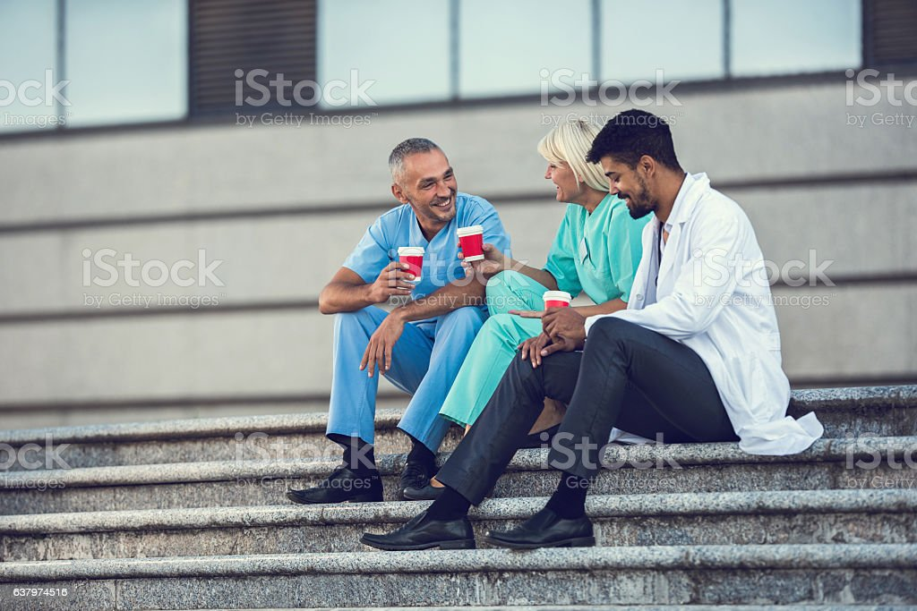 Happy doctors talking during a coffee break on stairs. stock photo