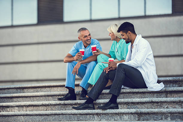 Happy doctors talking during a coffee break on stairs. - foto de stock