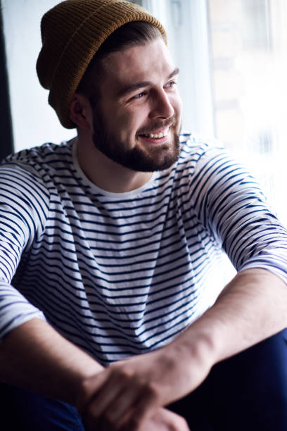 Happy dreamy young bearded sailor in workwear sitting on window sill and contemplating seascape Dreamy bearded sailor sailor suit stock pictures, royalty-free photos & images