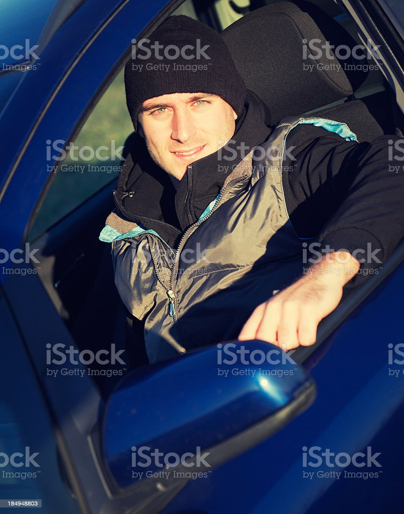 Happy driver in his blue car royalty-free stock photo