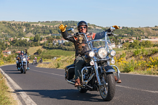 Riolo Terme (RA) Italy - September 22, 2013: a happy driver leads a group of bikers riding Harley Davidson at motorcycle rally \