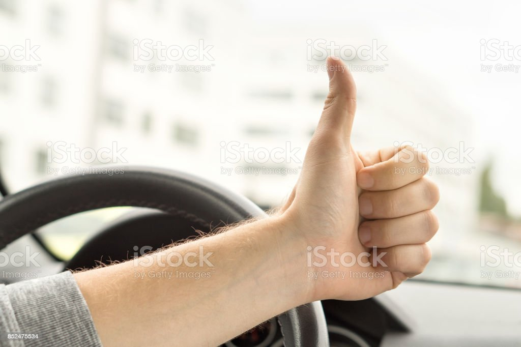 Happy driver showing thumbs up in car. Satisfied with new car or no traffic. Passed driving school test or vehicle inspection. Vehicle fixed and repaired. stock photo