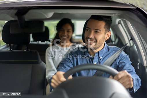Happy Latin American driver transporting a woman in a car while talking to her - transportation concepts