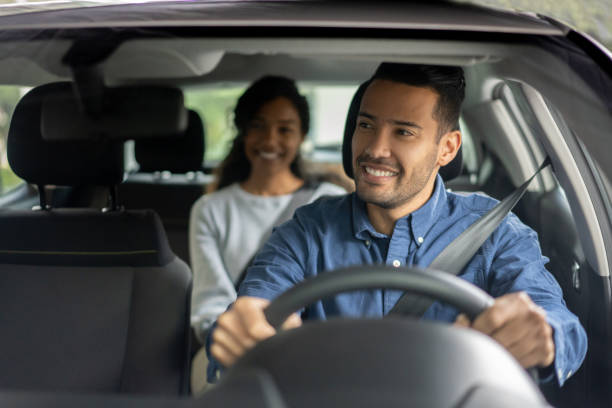 Happy driver transporting a woman in a car stock photo