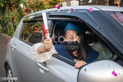 Shot of a happy East Asian graduate with face mask,  showing her rolled up certificate outside her window car, during the graduation parade around neighbourhood amidst Covid 19 pandemic