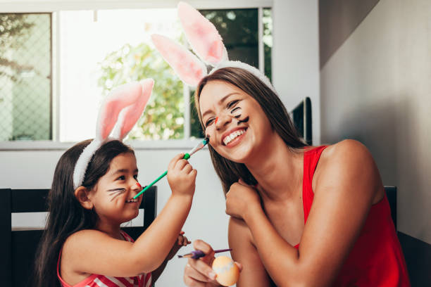 ¡ feliz pascua! una madre y su hija pintan huevos de pascua. feliz familia preparando para la pascua. linda niña niño usando orejas de conejo en el día de pascua - pascua fotografías e imágenes de stock