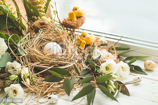istock Happy Easter background. Easter egg in a nest with floral decoration near the window. Quail eggs. Happy Easter concept 1134245560