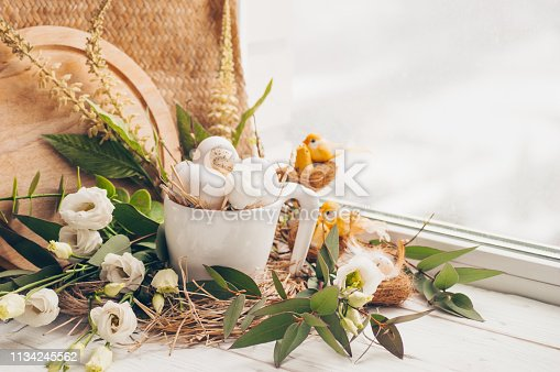 istock Happy Easter background. Easter egg in a nest with floral decoration near the window. Quail eggs. Happy Easter concept 1134245562