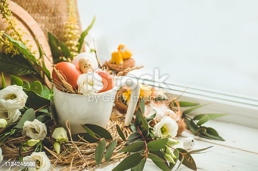 istock Happy Easter background. Easter egg in a nest with floral decoration near the window. Quail eggs. Happy Easter concept 1134245566