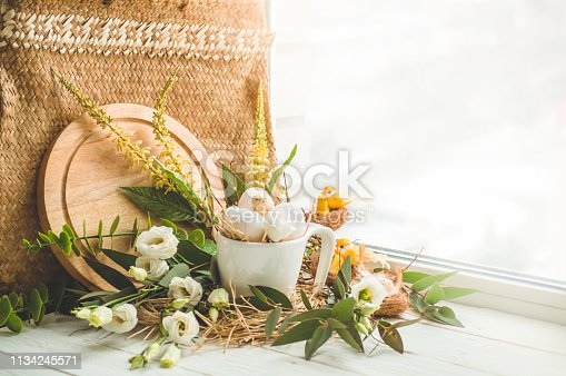 istock Happy Easter background. Easter egg in a nest with floral decoration near the window. Quail eggs. Happy Easter concept 1134245571