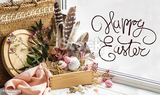 istock Happy Easter background. Pink Easter eggs in a nest with floral decorations and feathers near the window 1134245559
