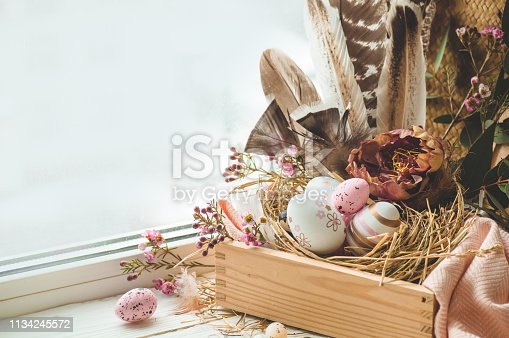 istock Happy Easter background. Pink Easter eggs in a nest with floral decorations and feathers near the window 1134245572