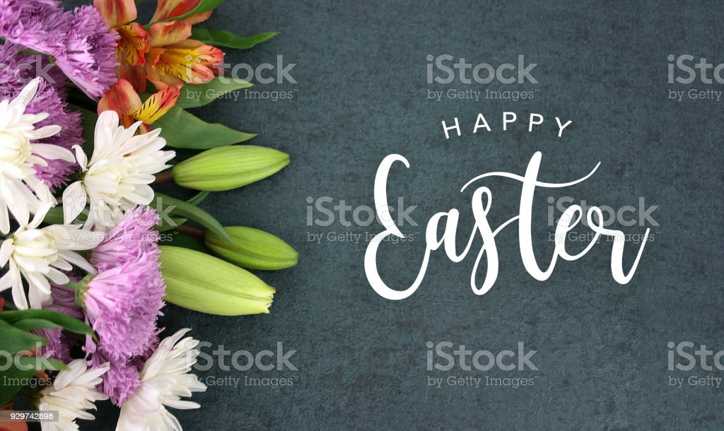 Happy Easter calligraphy over blackboard background with colorful flower blossom bouquet