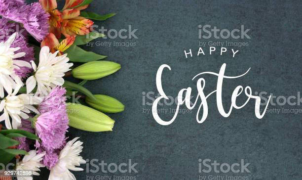 Spring season still life with Happy Easter calligraphy holiday script over dark blackboard background texture with beautiful colorful white, pink, orange, purple and green flower blossom bouquet on side, widescreen