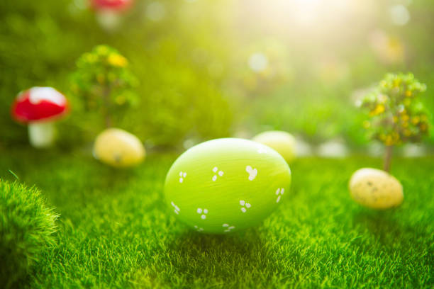 Happy Easter concept. Colorful easter eggs and one big green easter egg on spring green grass. Fairy tale sunset on the plastic green field with plastic grass, mushrooms and trees. Fake grass. Macro stock photo