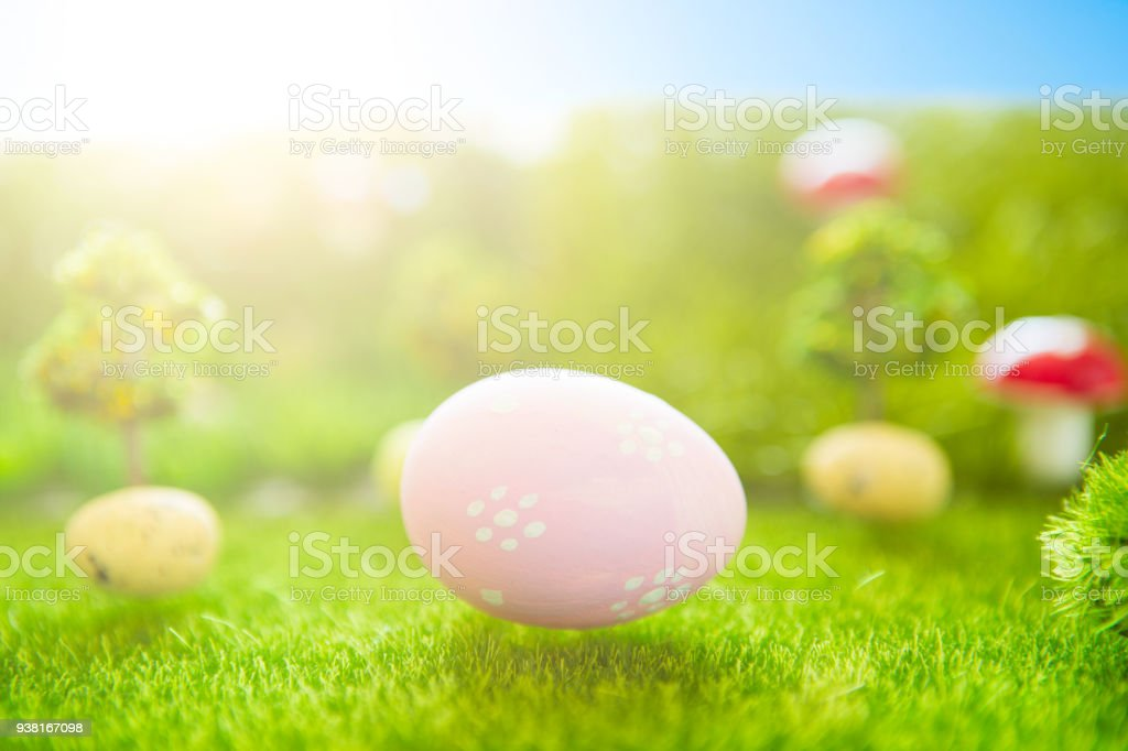 Happy Easter concept. Colorful easter eggs and one big pink easter egg on spring green grass. Fairy tale sunset on the plastic green field with plastic grass, mushrooms and trees. Fake grass. Macro stock photo