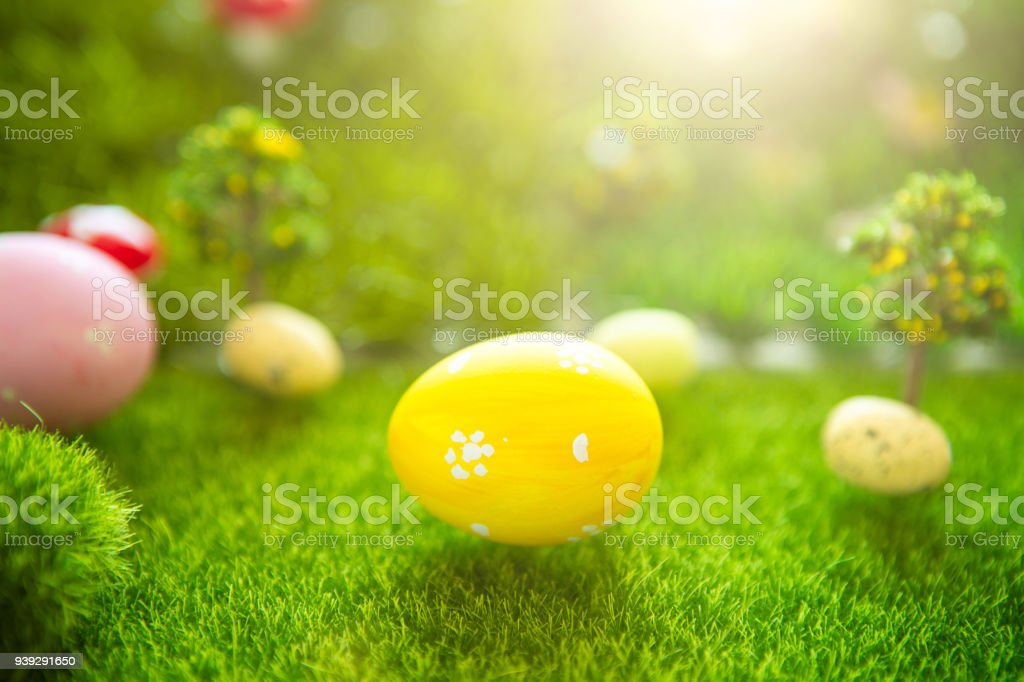 Happy Easter concept. Colorful easter eggs and one big yellow easter egg on spring green grass. Fairy tale sunset on the plastic green field with plastic grass, mushrooms and trees. Fake grass. Macro stock photo