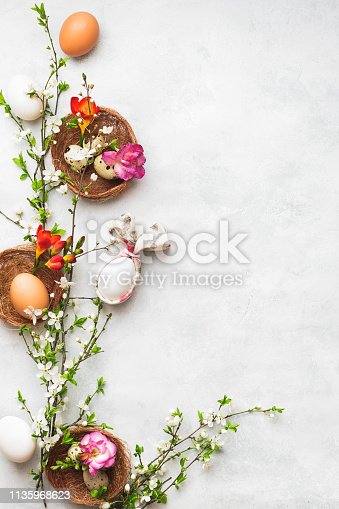 922661892 istock photo Happy Easter concept. Easter eggs with bunny ear napkin and spring cherry flowers on textured surface 1135968623