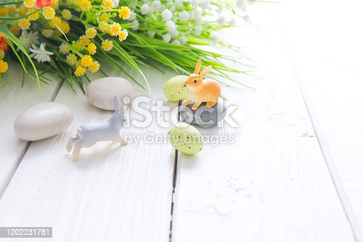 Happy Easter concept. Easter eggs with flowers and small bunny toys on wooden board, easter holiday concept.