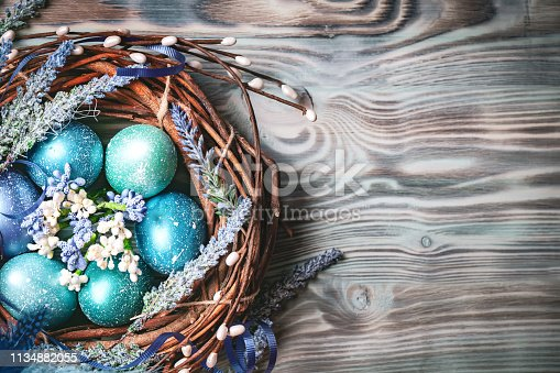 istock Happy Easter. Congratulatory easter background. Easter eggs and flowers. Background with copy space. Selective focus. 1134882055