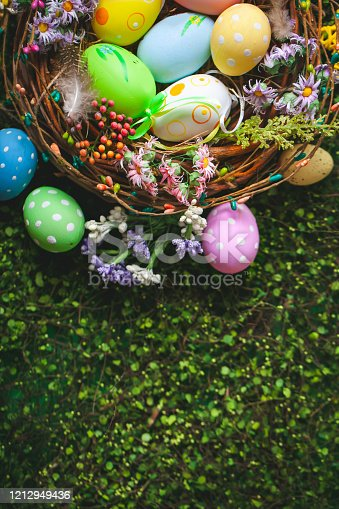 1138213028 istock photo Happy Easter. Congratulatory easter background. Easter eggs and flowers. Background with copy space. Selective focus. Top view. 1212949436