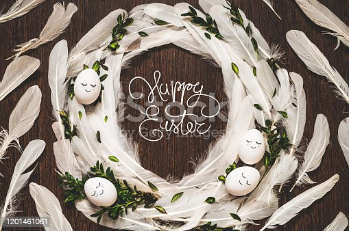 1135121547 istock photo Happy Easter. Congratulatory easter background. Easter eggs in white feathers on a wooden background 1201461061