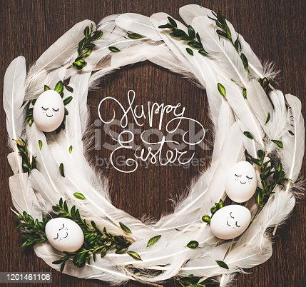 1135121547 istock photo Happy Easter. Congratulatory easter background. Easter eggs in white feathers on a wooden background 1201461108