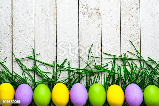 istock Happy easter eggs on wooden background, colorful eggs on white boards 923672066