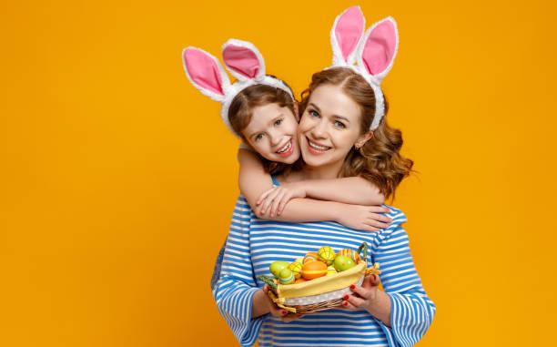 Frohe Ostern! Familie Mutter und Kind Tochter mit Ohren Hase immer bereit für den Urlaub auf farbigen gelben Hintergrund – Foto