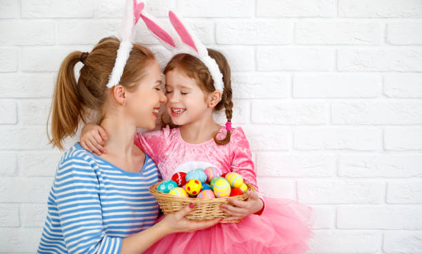 happy easter! family mother and child daughter with ears hare getting ready for holiday - easter foto e immagini stock