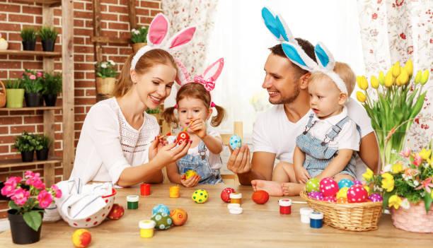 feliz páscoa! crianças, pai e mãe de família pintar ovos para férias - familia pascoa - fotografias e filmes do acervo