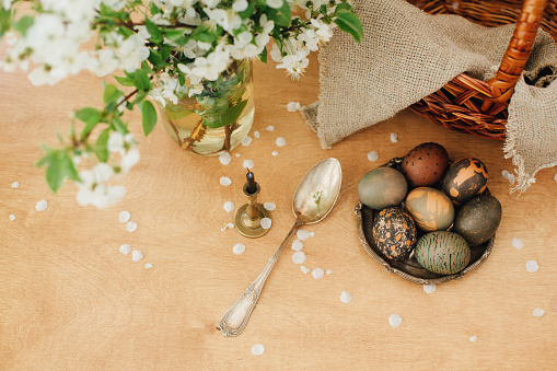 Happy Easter flat lay. Modern Easter eggs with spring flowers on rustic wooden table with basket. Stylish grey stone and green Easter eggs painted in natural dye from carcade tea.