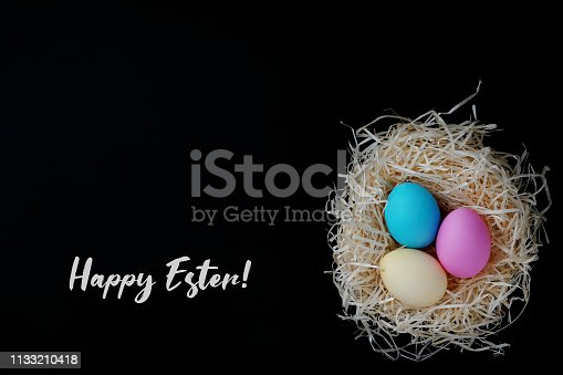 Nest of straw with colorful eggs, happy Easter. Concept Greeting card.