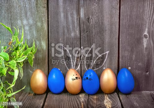 912300146 istock photo Happy Easter greeting card.Blue and gold eggs with cute Bunny ears on a rustic wooden background.Festive decoration.Spring holiday. Banner, Billboard for sale in the store, website.copy space. 1214495258