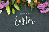 istock Happy Easter greeting over blackboard background with colorful flower blossom bouquet 931061852