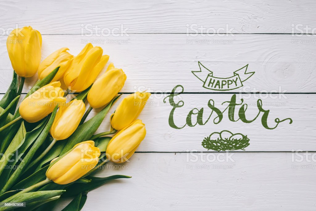 Happy easter hand lettering calligraphy text. Yellow tulips bunch on white wooden planks rustic barn rural table background. Letters, inscription. Beautiful horizontal flat lay postcard. stock photo