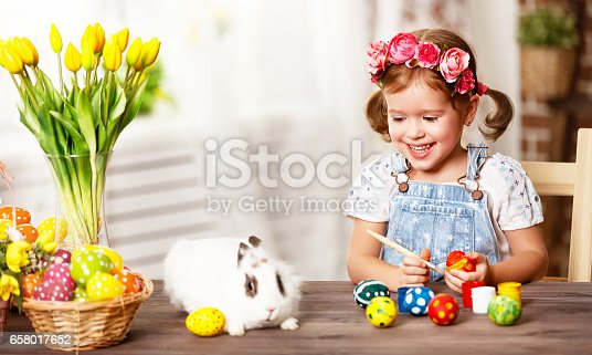 istock Happy easter! happy baby girl paints eggs for holiday 658017652