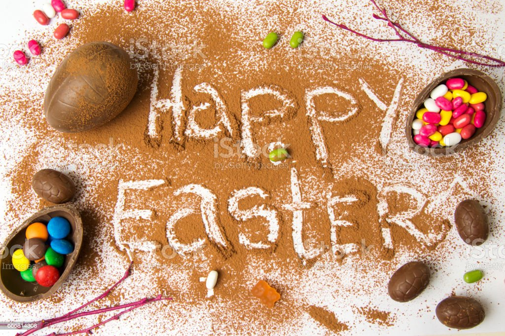 Happy Easter in cacao powder with chocolate eggs stock photo