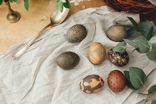 Happy Easter. Modern Easter eggs with eucalyptus on rustic wooden table. Stylish grey stone and green Easter eggs painted in natural dye from carcade tea. Stylish still life