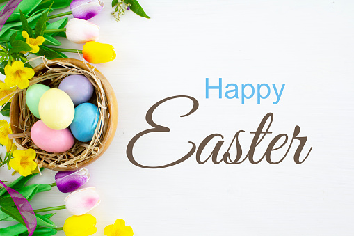 Happy Easter with easter eggs and spring flowers, on a white background.